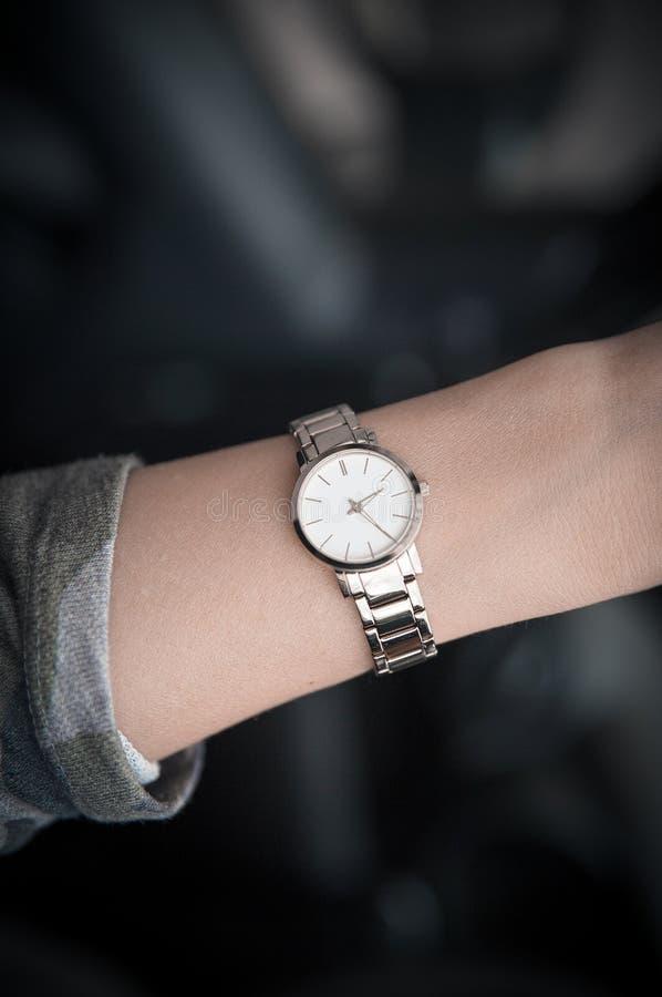 Het polshorloge van vrouwen op de hand van het meisje Het gouden horloge van vrouwen De tijd is geld royalty-vrije stock afbeelding
