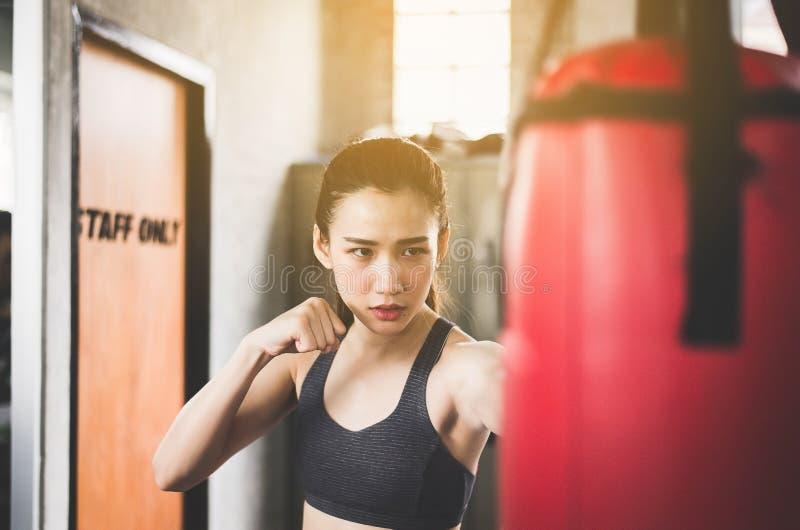 Het ponsen van de vrouwenbokser bij een het in dozen doen gymnastiek, Vrouwenbokser opleiding op ponsenzak royalty-vrije stock afbeelding
