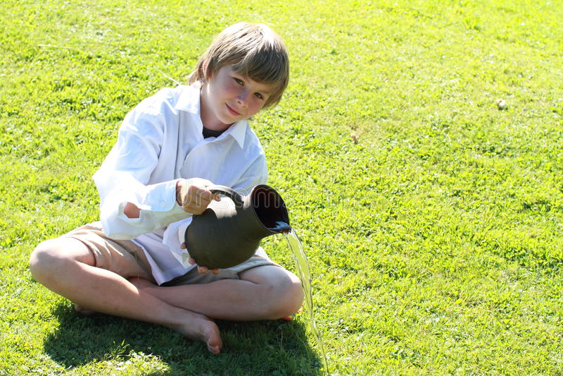 Het pooring water van de jongen van een waterkruik stock afbeelding