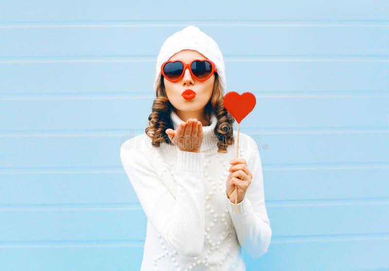Het portret de mooie vrouw die rode lippen blazen luchtkus verzendt houdt lollyhart die de zonnebril van een hartvorm, gebreide h royalty-vrije stock afbeelding