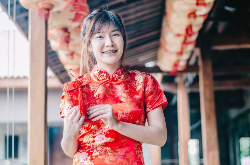 Het portret die de mooie Aziatische kleding van de vrouwenslijtage cheongsam charmeren krijgt rode enveloppen van haar familie He stock fotografie