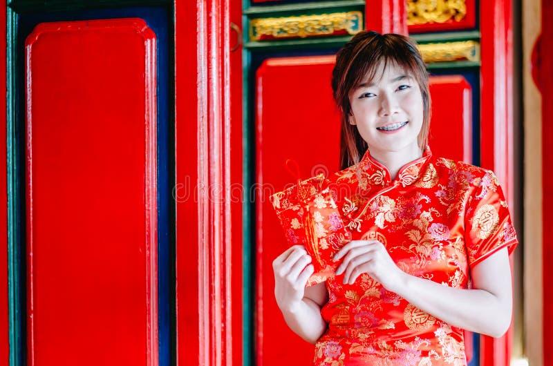 Het portret die de mooie Aziatische kleding van de vrouwenslijtage cheongsam charmeren krijgt rode enveloppen van haar familie He royalty-vrije stock afbeelding