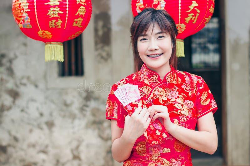Het portret die mooie Aziatische vrouwenslijtage charmeren cheongsam kleedt open omhoog de rode envelop met geld, in het Chinese  royalty-vrije stock afbeelding