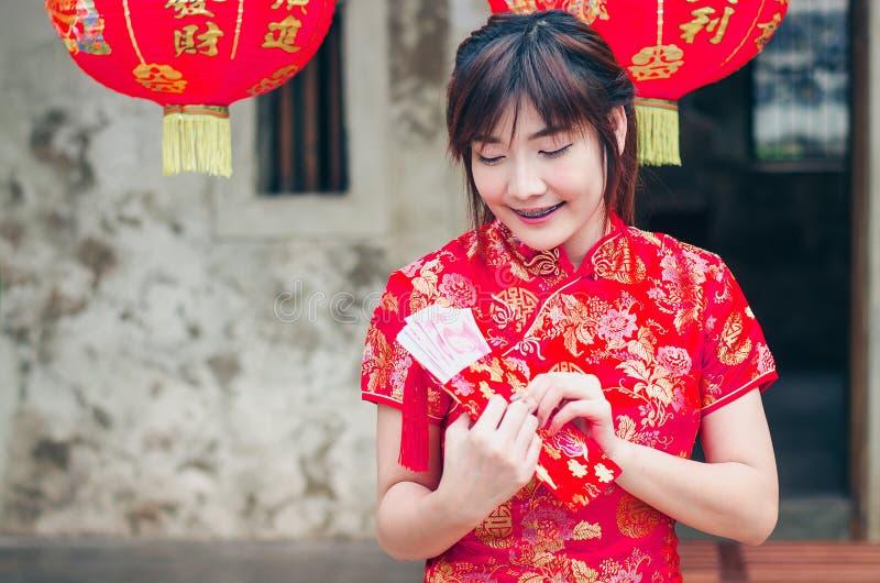 Het portret die mooie Aziatische vrouwenslijtage charmeren cheongsam kleedt open omhoog de rode envelop met geld, in het Chinese  royalty-vrije stock afbeeldingen