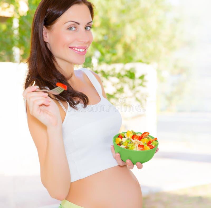 Zwangere vrouw die salade eten stock foto's