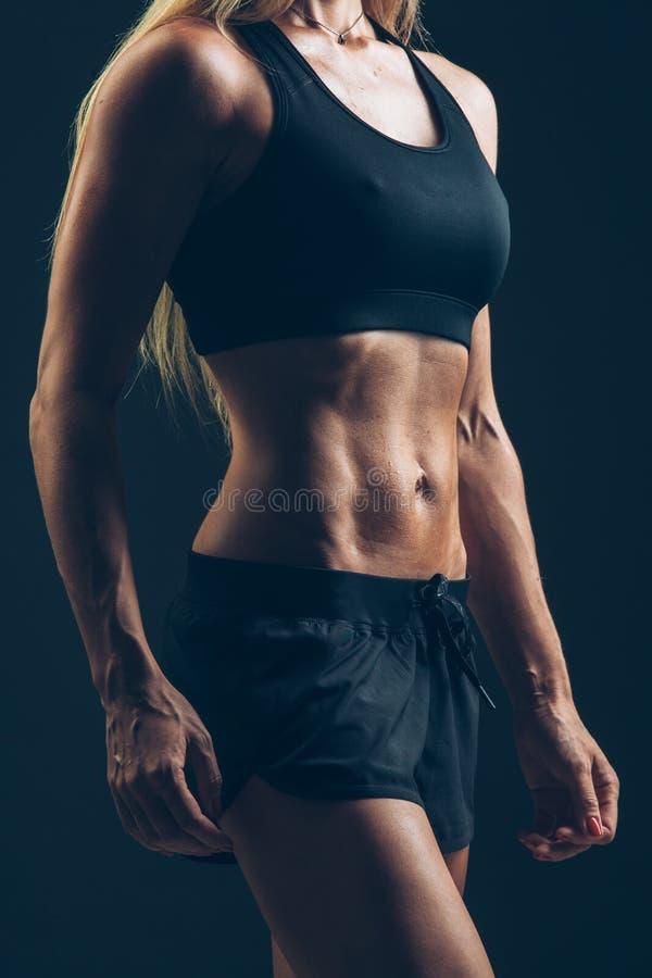 Het portret die van de sportenvrouw zwarte sportkleding over dark dragen royalty-vrije stock foto