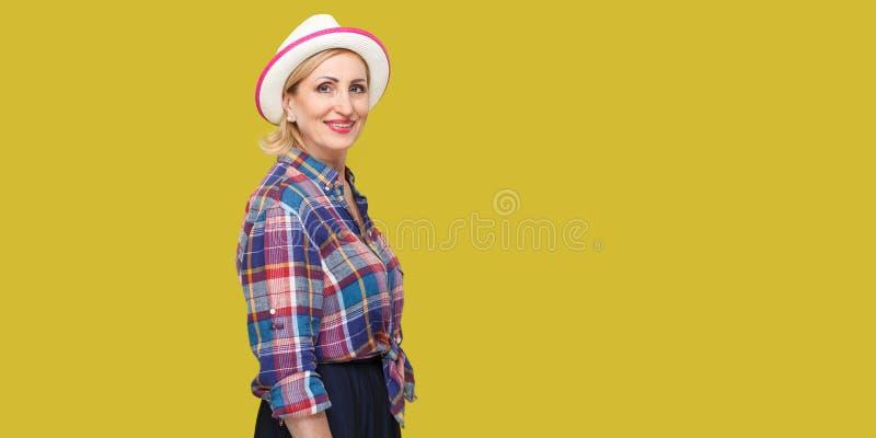 Het portret die van het profiel zijaanzicht van blije tevreden succesvolle modieuze rijpe vrouw in toevallige stijl met hoed die, royalty-vrije stock foto