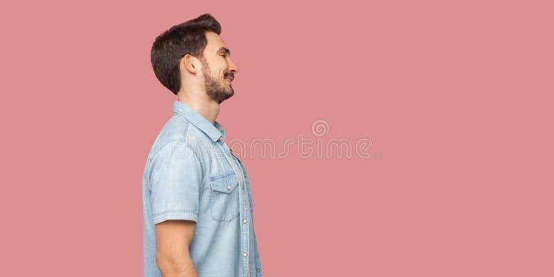 Het portret die van het profiel zijaanzicht van de gelukkige tevreden knappe gebaarde jonge mens in blauw toevallig overhemd die, royalty-vrije stock fotografie