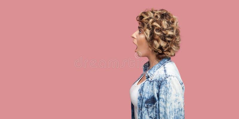 Het portret die van het profiel zijaanzicht van geschokte jonge vrouw met krullend kapsel in toevallig blauw overhemd die, voorui stock afbeelding