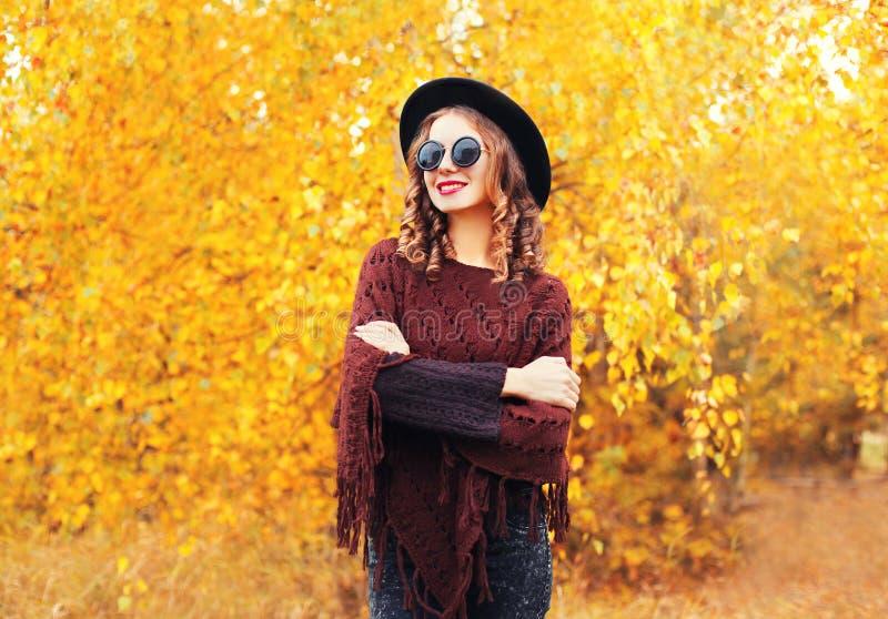 Het portret glimlachende vrouw die van de de herfstmanier zwarte hoedenzonnebril en gebreide poncho over zonnige gele bladeren dr royalty-vrije stock afbeelding