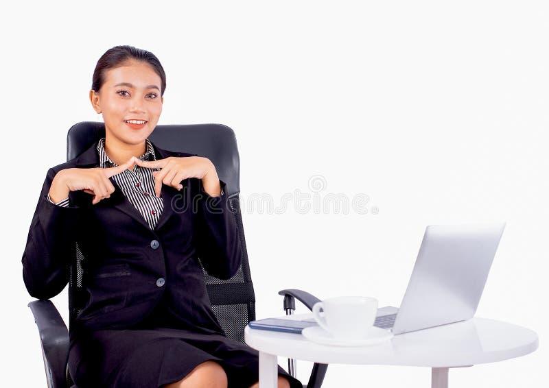 Het portret isoleerde Zuidoostaziatische bedrijfsvrouw draagt donkergrijs kostuum bekijkt de camera en zit op stoel met bureau royalty-vrije stock afbeeldingen