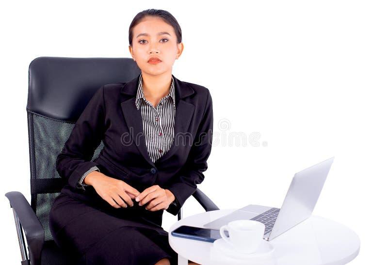 Het portret isoleerde Zuidoostaziatische bedrijfsvrouw draagt donkergrijs kostuum bekijkt de camera en zit op stoel met bureau stock fotografie