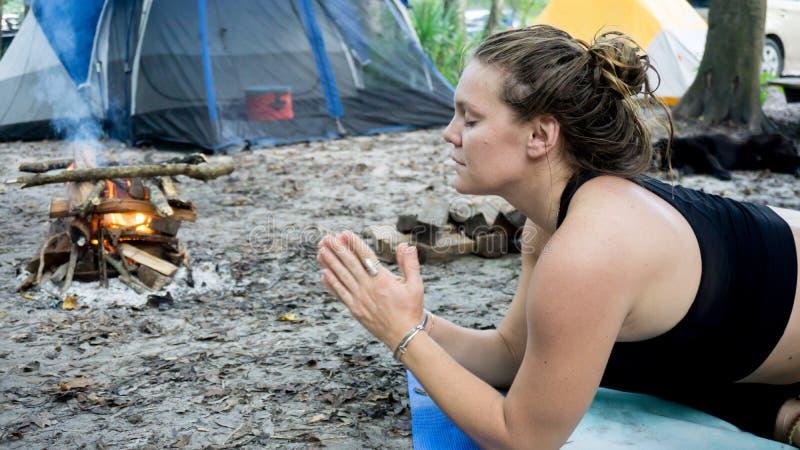 Het portret ot van een jonge vrouw met namastegebed stelt handen toguether yoga terwijl het kamperen in het bos stock afbeeldingen