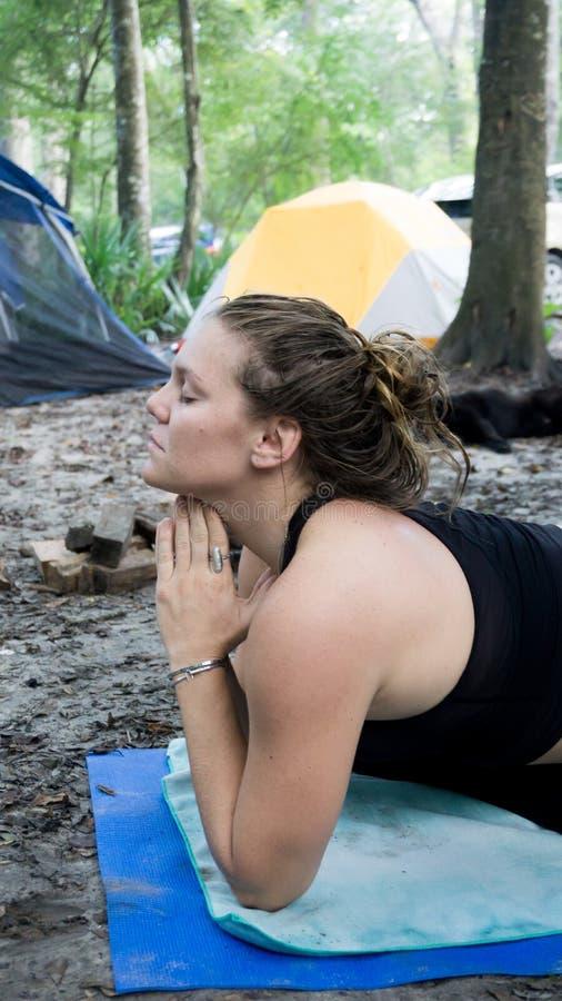 Het portret ot van een jonge vrouw met namastegebed stelt handen toguether yoga terwijl het kamperen in het bos stock foto's