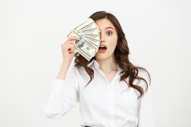 Het portret schokte jonge bedrijfsvrouw die en geld bevinden zich houden dat over witte achtergrond wordt geïsoleerd royalty-vrije stock foto's