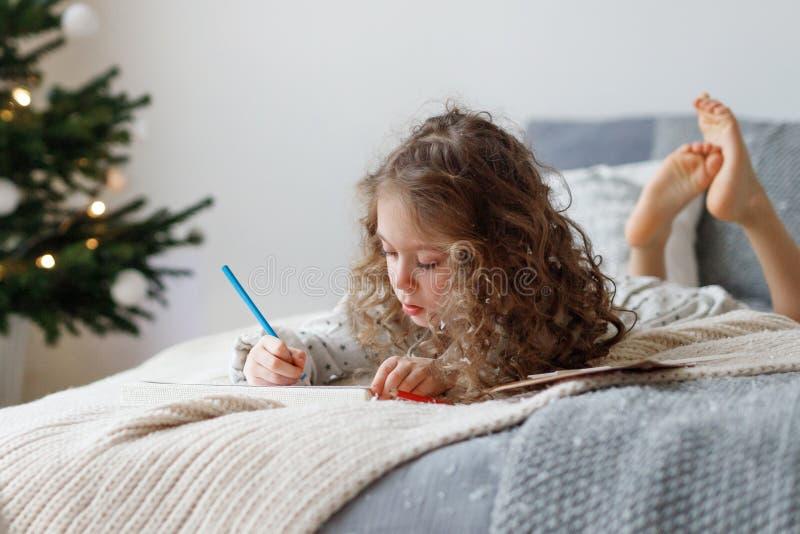 Het portret van aanbiddelijk krullend meisje brengt vrije tijd aan bed door, maakt Kerstkaart voor ouders, schrijft wensen en tre stock fotografie