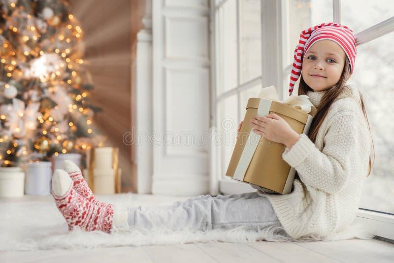 Het portret van aanbiddelijk prettig kijkend meisje draagt comfortabele warme kleren, houdt verpakte giftdoos, ontvangt gelukwens royalty-vrije stock foto's