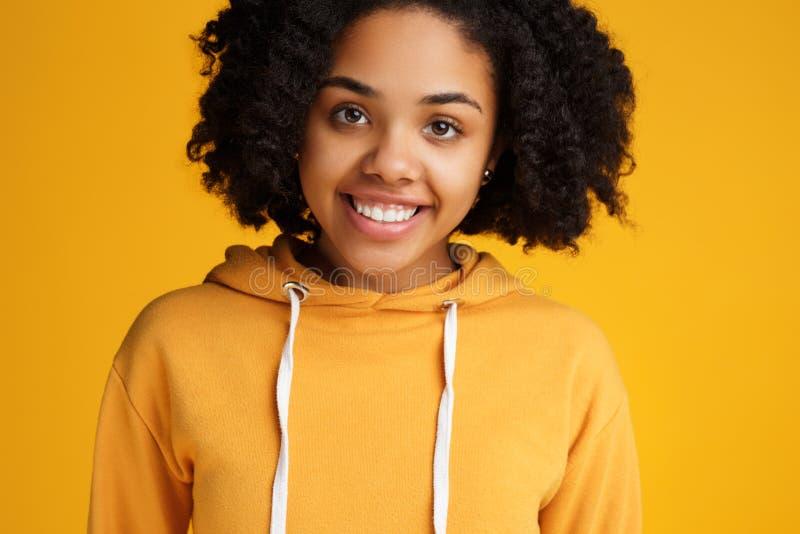 Het portret van aantrekkelijke Afrikaanse Amerikaanse jonge vrouw met mooie glimlach kleedde zich in vrijetijdskleding over geel royalty-vrije stock afbeelding