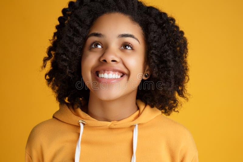 Het portret van aantrekkelijke Afrikaanse Amerikaanse jonge vrouw met mooie glimlach kleedde zich in vrijetijdskleding over geel royalty-vrije stock afbeeldingen