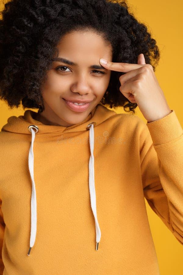 Het portret van aantrekkelijke Afrikaanse Amerikaanse jonge vrouw met mooie glimlach kleedde zich in vrijetijdskleding over geel stock afbeeldingen