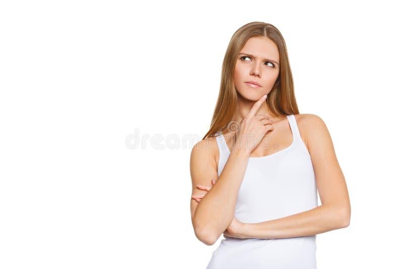 Het portret van aantrekkelijke tiener denkt omhoog het kijken, slijtage wit die overhemd, over witte, jonge mooie vrouw wordt geï stock afbeelding