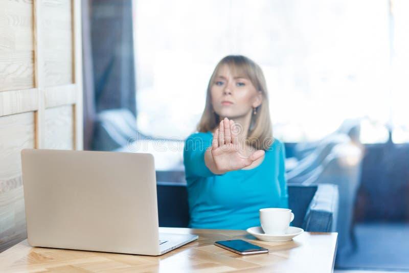 Het portret van agressief ongelukkig jong meisje freelancer met blondehaar in blauwe blouse zit in koffie en heeft slechte stemmi stock foto's