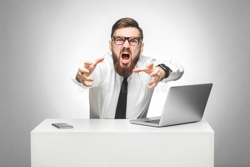 Het portret van agressieve boze jonge zakenman in wit overhemd en de avondkleding beschuldigen u in bureau en hebben slechte stem stock foto