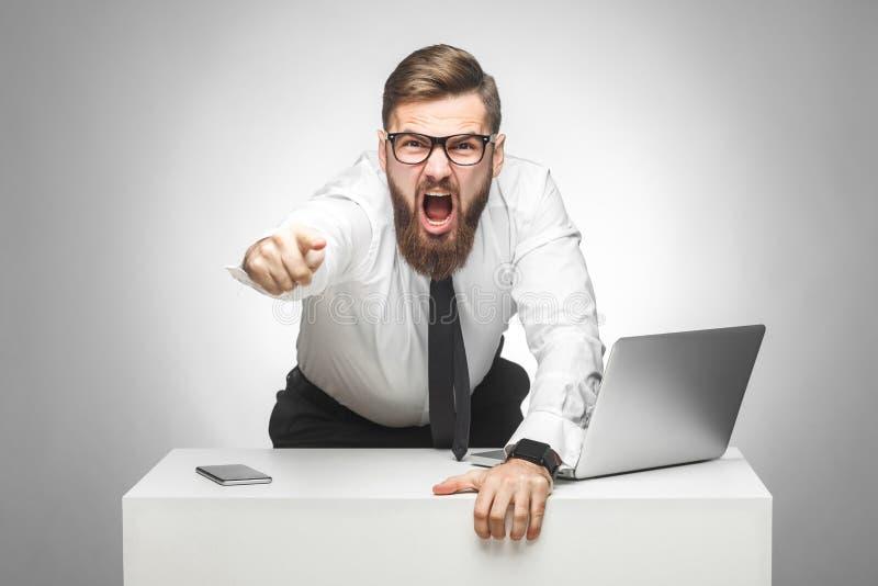 Het portret van agressieve ongelukkige jonge zakenman in wit overhemd en de avondkleding beschuldigen u in bureau en hebben slech royalty-vrije stock foto's