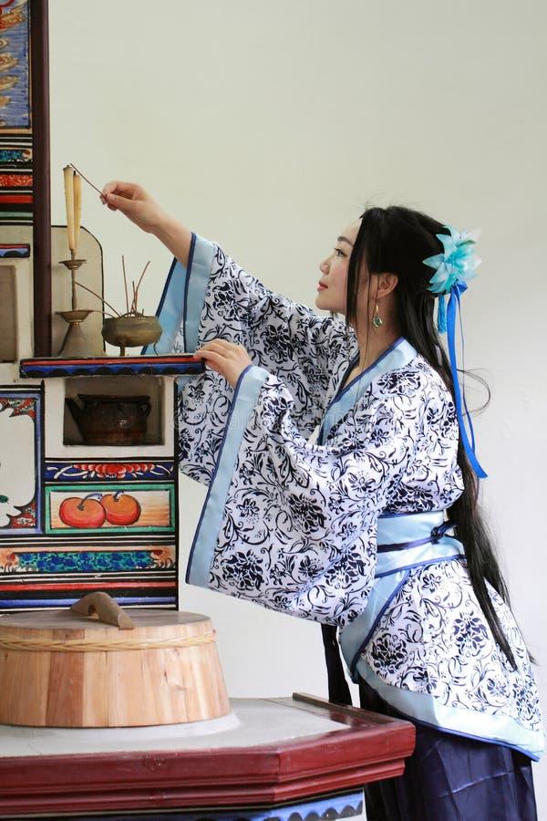 Het portret van Aziatisch Chinees meisje in traditionele kleding, draagt blauwe en witte porseleinstijl Hanfu, lichte kaarsen in  royalty-vrije stock afbeelding