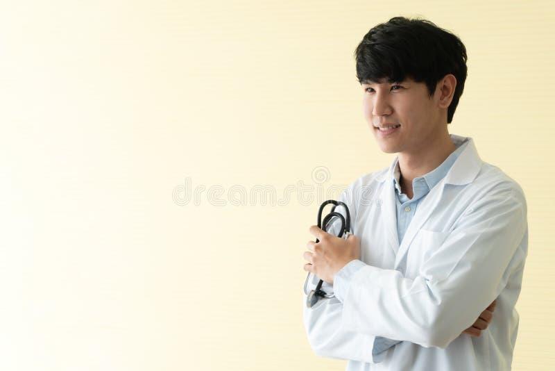 Het portret van Aziatische jonge arts met wapens kruiste holdingsstethoscoop in de overlapping van de het ziekenhuisnoodsituatie  stock foto's