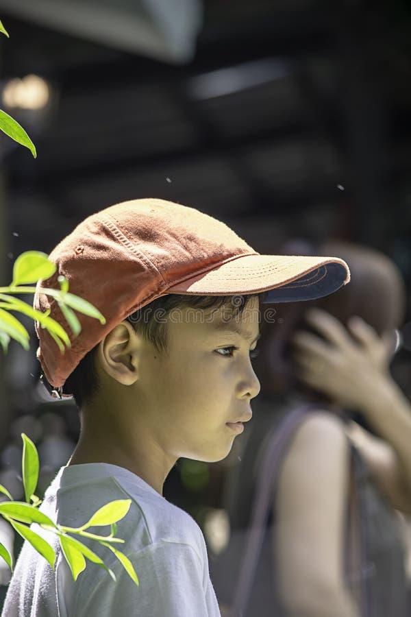 Het portret van Aziatische jongen die een rood GLB en een wit overhemd dragen is glimlach royalty-vrije stock afbeelding