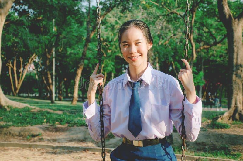Het portret van Aziatische studente die in stijl van school de eenvormige Thailand, op schommeling zitten en geniet zich van in w royalty-vrije stock foto