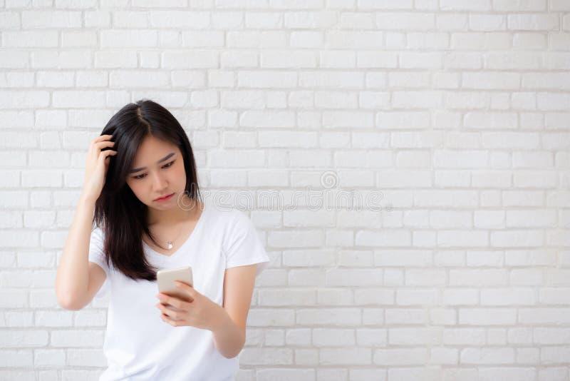 Het portret van Aziatische vrouw bored en is met iets niet bevallen die smartphone kijken die zich op de achtergrond van de cemen stock foto's
