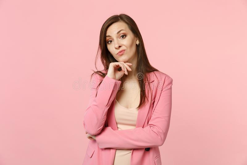 Het portret van betrokken jonge vrouw die jasje dragen zette handsteun op kin op kijkend camera op pastelkleurroze stock fotografie