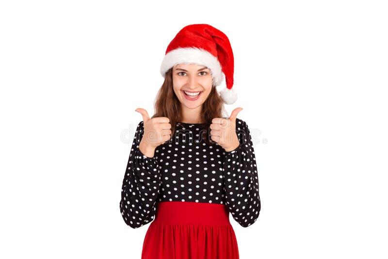 Het portret van het blije toevallige meisje tonen beduimelt omhoog emotioneel meisje in Kerstmishoed van de Kerstman dat op witte stock foto's
