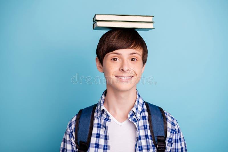 Het portret van het charmeren van jongen zette literatuur op zijn hoofd die gecontroleerde de rugzakrugzak dragen van de overhemd royalty-vrije stock afbeeldingen