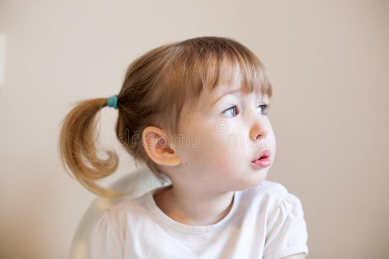 Het portret van het close-upgezicht van grappige twee jaar oud wit meisjes op muurachtergrond royalty-vrije stock afbeeldingen