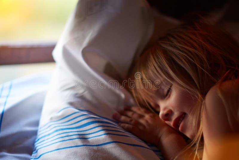 Het portret van het close-upprofiel van mooi blond Kaukasisch meisje met gesloten ogen dichtbij een venster met witte gordijnen royalty-vrije stock foto's