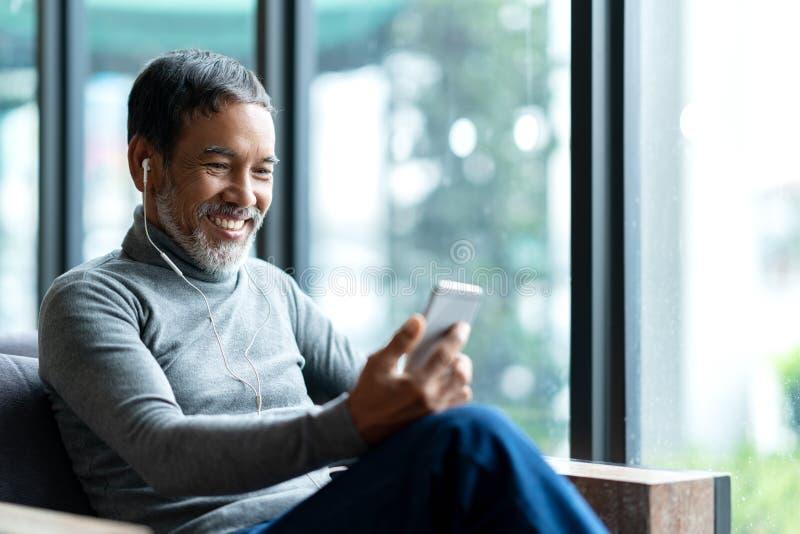 Het portret van de aantrekkelijke rijpe Aziatische mens trok zich met modieuze korte baard terug gebruikend smartphone zitting of stock afbeelding