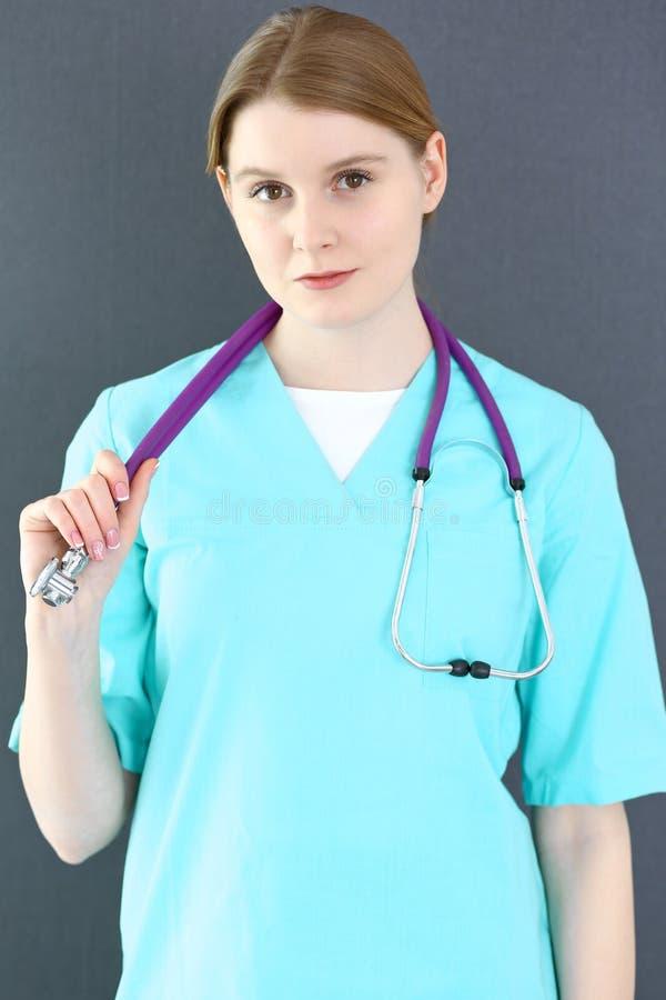 Het portret van de artsenvrouw met stethoscoop Jonge vrouwelijke chirurg of verpleegster die zich dichtbij grijze muur in kliniek royalty-vrije stock afbeeldingen