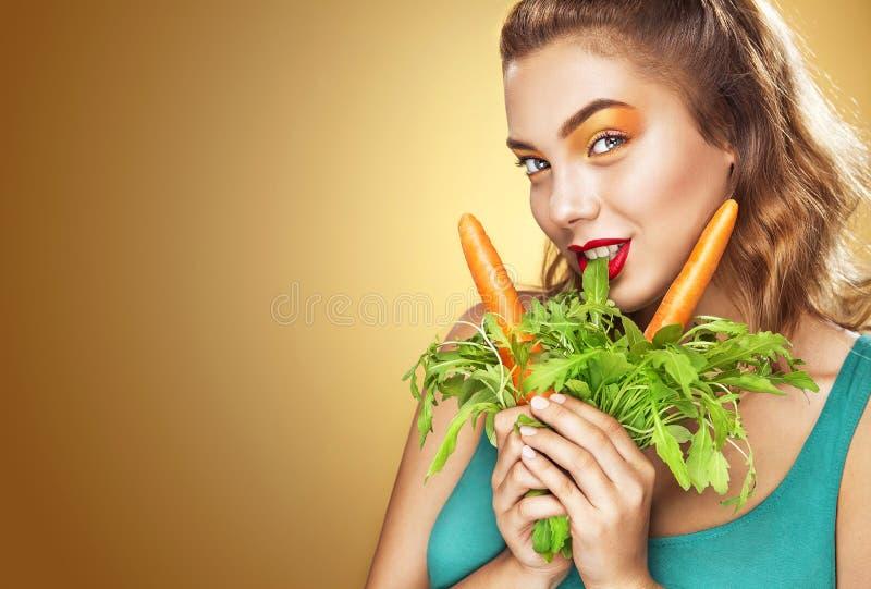 Het portret van de close-up Mooie blonde jonge vrouw die pret hebben die vegetarisch voedsel eten - wortel royalty-vrije stock foto