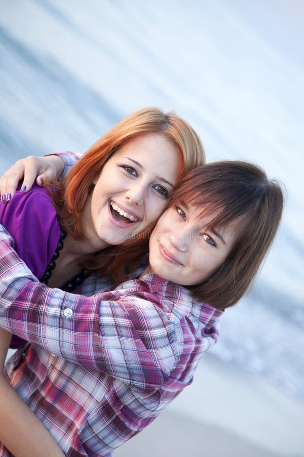 Het portret van de close-up van twee gelukkige meisjes op het strand royalty-vrije stock fotografie