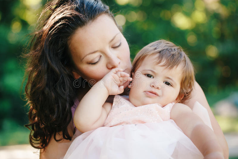 Het portret van de close-upgroep van mooie witte Kaukasische donkerbruine moederholding die dochter koesteren die haar kussen in  royalty-vrije stock foto