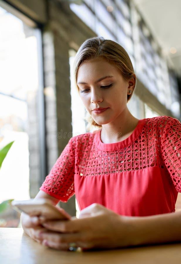 Het portret van de close-uplevensstijl van jonge blonde Kaukasische natuurlijke millennial vrouw die aan cellphone bij moderne tr stock fotografie