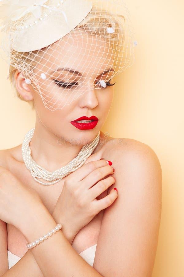 Het portret van de close-upschoonheid van jonge vrouw met rode lippen, lange valse wimpers en witte retro hoed met netwerk stock fotografie