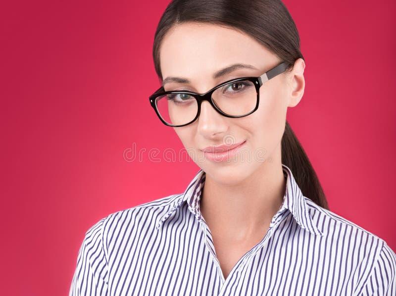 Het portret van de close-upstudio van jonge aantrekkelijke vrouw met glazen op een rode achtergrond stock foto