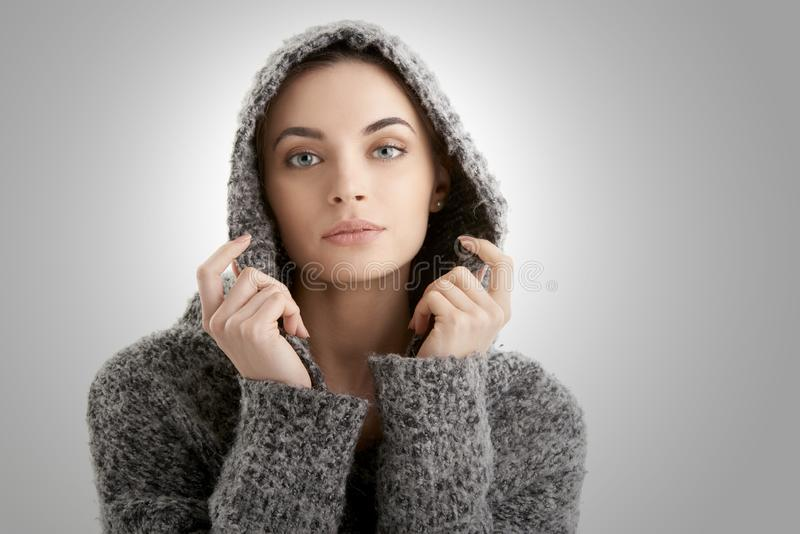 Het portret van de close-upstudio van het mooie jonge vrouw dragen hoodie terwijl het stellen bij geïsoleerde witte achtergrond royalty-vrije stock foto's
