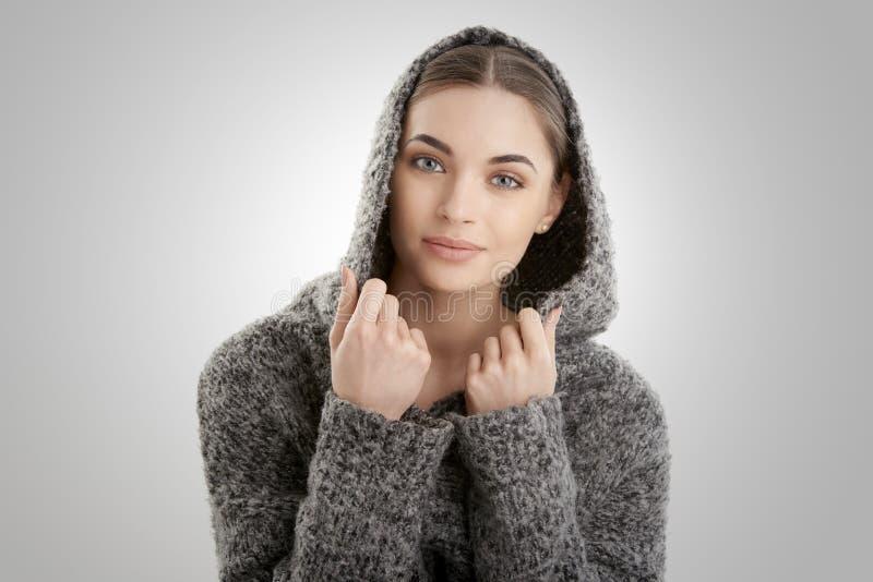 Het portret van de close-upstudio van het mooie jonge vrouw dragen hoodie terwijl het stellen bij geïsoleerde witte achtergrond stock fotografie