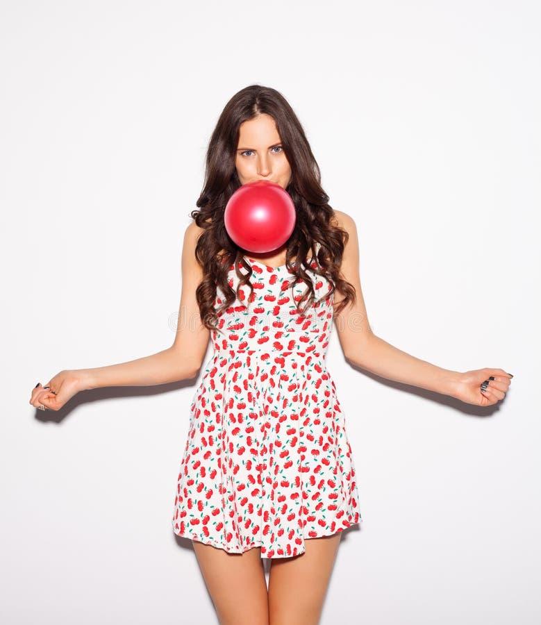 Het portret van de close-upstudio van mooi donkerbruin meisje die een rode ballon blazen die korte die kersenkleding dragen en ha stock afbeelding
