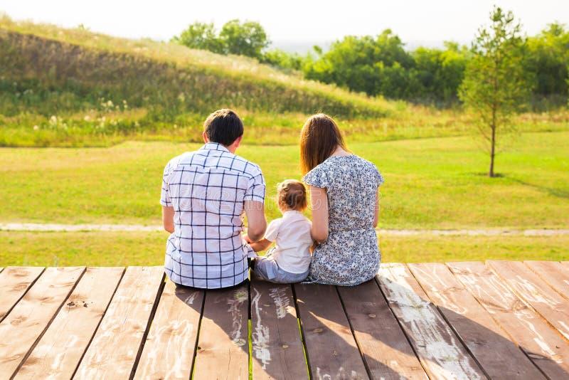 Het portret van de familie Beeld van gelukkige houdende van vader, moeder en hun baby in openlucht Papa, mamma en kind tegen groe stock foto's